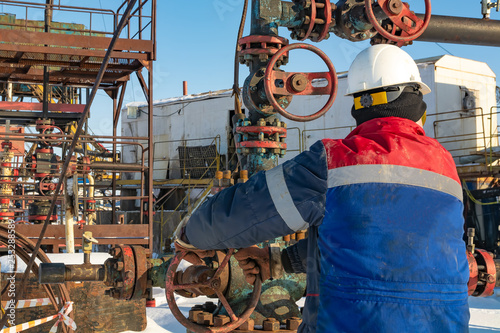 obraz lub plakat An employee of an oil company performs work on the well. Rotates the steering wheel on the fountain fittings. In the background equipment for oil production. Winter day at the polar oil field.