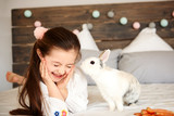 Fototapeta Zwierzęta - Shot of rabbit kissing happy girl © gpointstudio