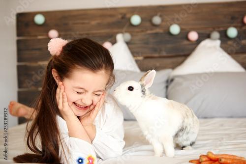 Shot of rabbit kissing happy girl - 253289332