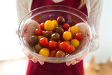 Woman hands holding different types of cherry tomatoes in round bowl at home.
