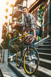 A handsome young man goes to the city ride with his bike, standing beside it and thinking about where he would go.