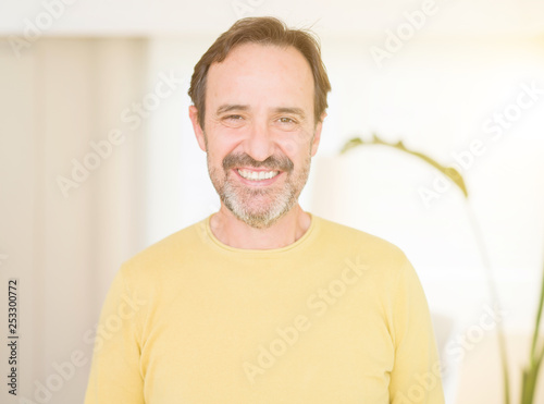 Leinwanddruck Bild Handsome middle age man smiling looking at the camera at home