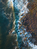 Top down view of wave coming into rocks.