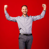 man raising arms fists up isolated on red background. emotion concept.