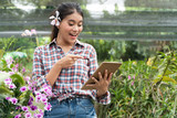 Female gardeners wear plaid shirts. There were orchids picking up the ears, the hand holding the tablet and pointing fingers on the tablet and smiling with joy.