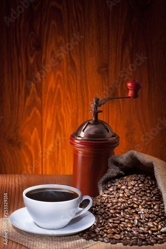 Cup of coffee with roasted beans and coffee grinder.