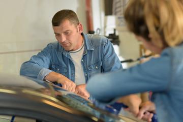 mle and female mechanics fitting a new car windscreen