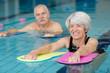 Leinwanddruck Bild - happy senior couple taking swimming lessons