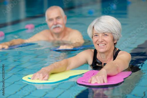 Leinwanddruck Bild happy senior couple taking swimming lessons