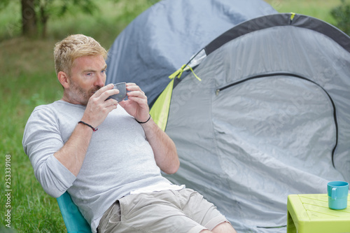 man drinks coffee next to his tent - 253339108