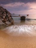 Beautiful sandy beach with rocks in the sea small bridge and a boat at dusk time, blue hour, Stoupa, Peloponnese, Greece.