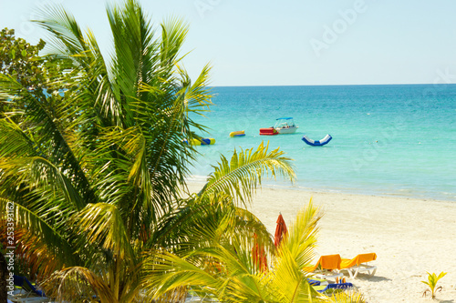 Fototapeten Strand beautiful tropical sandy beach with palms and boat in turquise caribbean sea at Jamaica