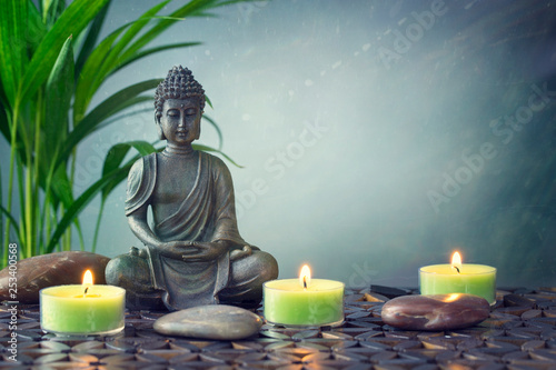 Leinwanddruck Bild Buddha statue  on a grey background