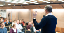 """Постер, картина, фотообои """"Expert giving a talk on business conference workshop. Unrecognizable people in audience at the conference hall. Business and entrepreneurship event."""""""