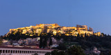 Acropolis of Athens Greece rock and Parthenon illuminated, blue sky background late in the evening.