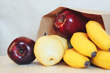 A paper bag with purchases from the store. Fresh fruits on the table.