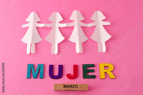 Paper doll chain and mujer made from colorful letters on pink background - 253421998