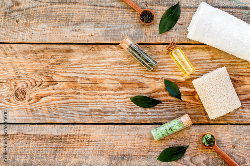 Tea tree spa composition. Fresh tea tree leaves, natural cosmetics, towel on rustic wooden background top view copy space border