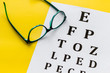 Eye examination. Eyesight test chart and glasses on yellow background