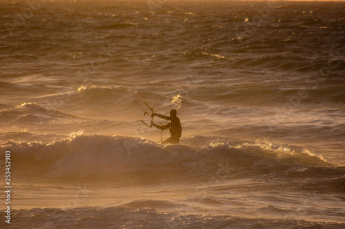 Surfer at sunset on a calm ocean - 253452903