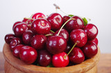 Sweet cherry fruits with leaves in a wooden bowl on a white background