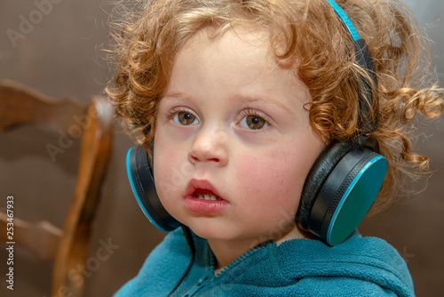 little boy listening to music with headphones - 253467933