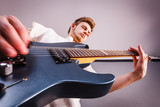Young man is playing electric guitar