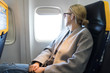 Leinwanddruck Bild - Thoughtful blonde casual caucasian woman wearing glasses, looking through the window while traveling by airplane. Commercial transportation by planes.