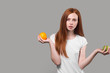 serious slim girl in white T-shirt holding an orange and apple.diet concept, body care. woman leads healthy lifestyle