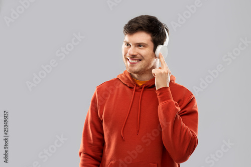 music, technology and people concept - happy young man in headphones and red hoodie over grey background - 253496137
