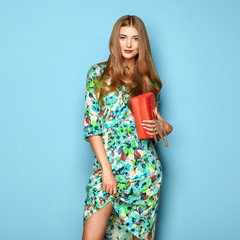 Blonde Young Woman in Floral Spring Summer Dress. Girl Posing on a Blue Background. Summer Floral Outfit. Stylish Wavy Hairstyle. Fashion Photo. Glamour Lady with Red Handbag