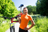 fitness, sport and healthy lifestyle concept - happy young man with bicycle outdoors in summer