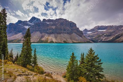 Leinwanddruck Bild  Bow Lake, surrounded by pine trees