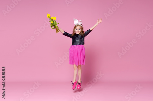 Cheerful baby girl jumping with a bouquet of yellow tulips on a pink background. Holidays, fashion and red concept. - 253515535