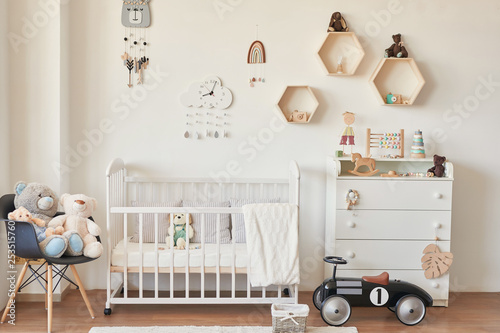 wooden toys in the children's room, chest of drawers and a white bed, the interior of the children's bedroom