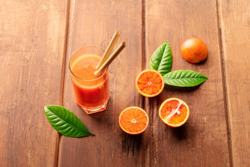 A glass of fresh orange juice with blood oranges, green leaves, and two bamboo straws, on a dark wooden background with a place for text © laplateresca