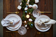 top view of quail eggs on napkin and plates near green moss, candles and crystal glasses on wooden table
