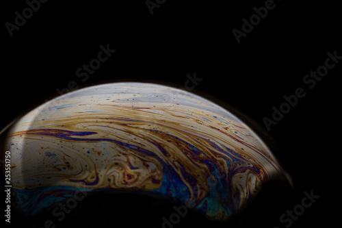 A bubble in rainbow colors on a black background. - 253551750