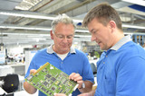 Fertigung von Elektronik: Teamwork Besprechnung und Qualitätskontrolle in einer Hi Tech Fabrik // Manufacturing of electronics: Teamwork discussion and quality control in a Hi Tech factory