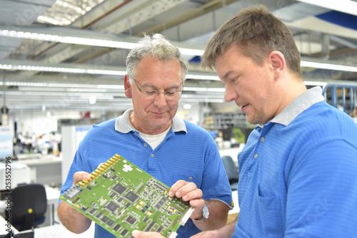 Leinwanddruck Bild Fertigung von Elektronik: Teamwork Besprechnung und Qualitätskontrolle in einer Hi Tech Fabrik // Manufacturing of electronics: Teamwork discussion and quality control in a Hi Tech factory