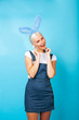 Leinwandbild Motiv young pretty blond girl with rabbit ears posing cheerful on blue background, lifestyle people concept