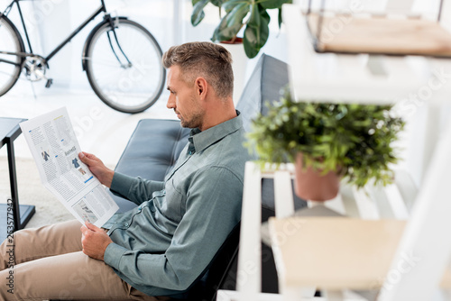 Leinwanddruck Bild selective focus of businessman reading business newspaper in office
