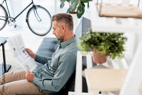 Leinwandbild Motiv selective focus of businessman reading business newspaper in office