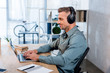 Leinwandbild Motiv cheerful businessman listening music in headphones while using laptop in modern office