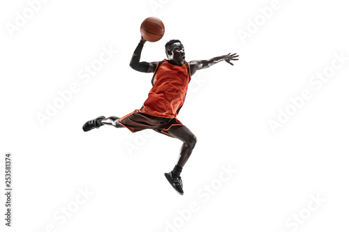 Leinwanddruck Bild Full length portrait of a basketball player with a ball isolated on white studio background. advertising concept. Fit african anerican athlete jumping with ball. Motion, activity, movement concepts.