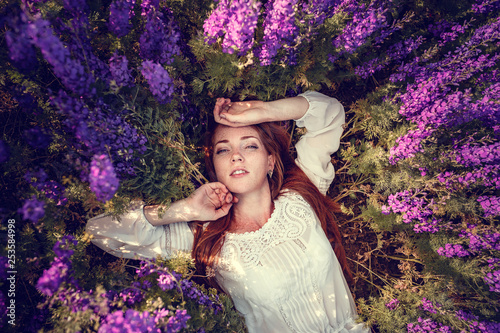 beautiful woman on purple background. woman with purple flowers - 253584998