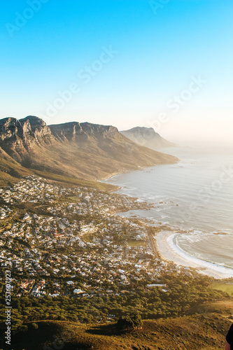 View of the 12 apostles and Camps Bay seen from the peak of Lions Head lookout point at sunset. - 253607923