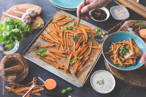 Frische süsskartoffeln mit gemüseschäler. Vegetarisches gericht zubereitung. pommes - 253650965