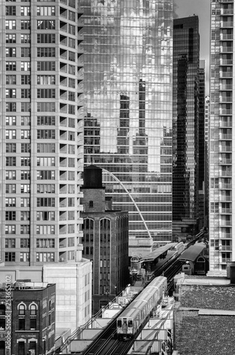 An elevated train is traveling between skyscrapers above Lake Street in the West Loop. Main streets in Chicago, streets in Illinois. Modern architecture and transportation. Black and white. © A McMullen