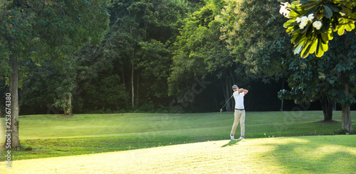 Young Asian man playing golf on a beautiful natural golf course - 253674380